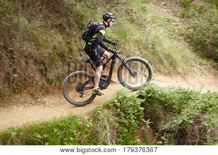Young Caucasian Professional Rider Performing Mountain Biking Stunts On Two-wheeled Motor-powered Bi
