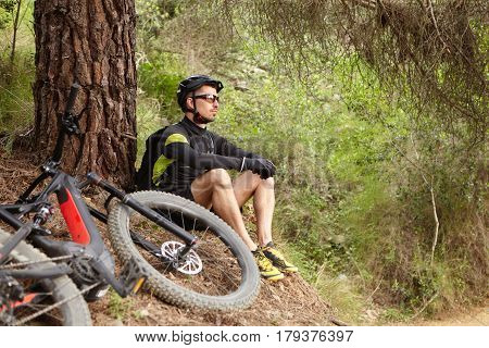 Attractive Young European Rider In Protective Gear Sitting On The Ground At Tree, Contemplating Amaz