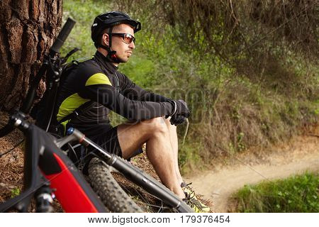 Sideways Shot Of Attractive Happy Young European Cyclist In Protective Equipment Sitting Under Tree