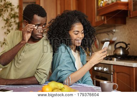 Jealous Curious Black Man Holding Glasses Spying His Girlfriend's Mobile Phone While She Is Typing M