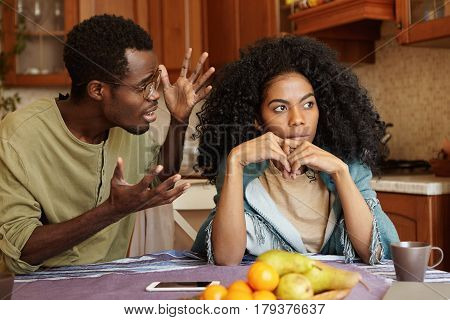 People And Relationships Concept. African American Couple Arguing In Kitchen: Man In Glasses Gesturi