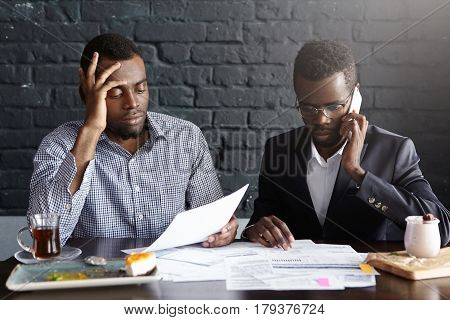 Candid Shot Of Serious Afro-american Colleagues In Formal Wear Working Together In Office: Man In Sh