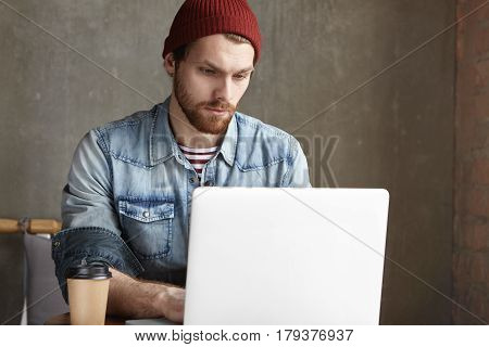 Serious Handsome Young European Freelancer Dressed In Trendy Clothing Working Remotely On Laptop Com