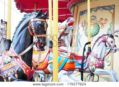 Beautiful horse carousel in a holiday park. Three horses on a traditional fairground vintage carousel. Merry-go-round with horses.