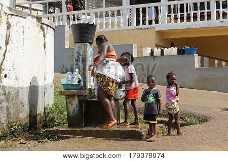SANTANA, SAO TOME - JANUARY 29, 2017: Family on public water pump on January 29, 2017 in Santana, Sao Tome, Africa