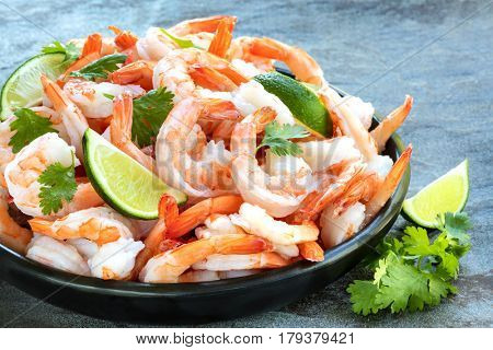 Platter of cooked shrimps with lime and cilantro, over slate.