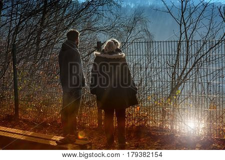 Two people on foggy morning standing at a precipice