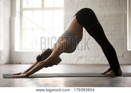 Young attractive woman practicing yoga, standing in Downward facing dog exercise, adho mukha svanasana pose, working out, wearing sportswear bra and pants, full length, white loft studio background