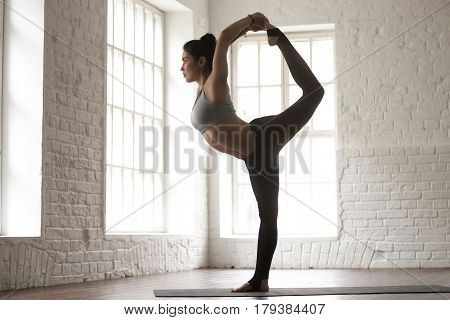 Young beautiful yogi woman practicing yoga concept, standing in Natarajasana exercise, Lord of the Dance pose, working out wearing sportswear, white loft studio background, full length, side view