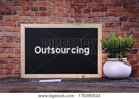Outsourcing Word On Blackboard With Green Plant.