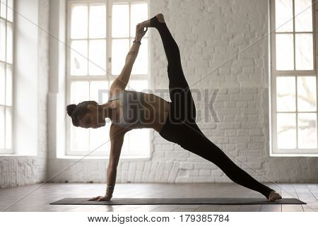 Young yogi woman practicing yoga concept, standing in Full Version of Vasisthasana exercise, Side Plank pose, working out, wearing sportswear, full length, white loft studio background, side view