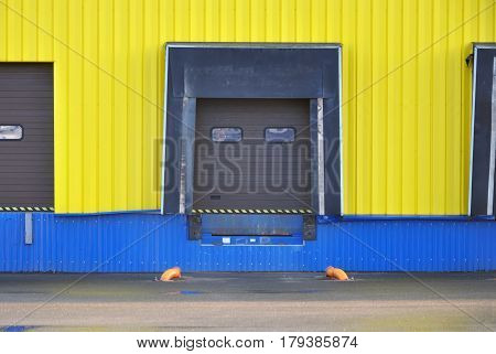 Facade of modern warehouse of yellow sandwich panels with airtight door gates (dock shelter). Front view.