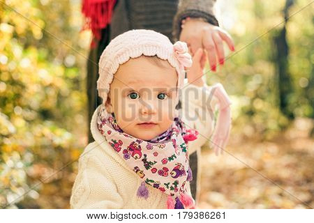 Little girl holding mothers hand. Toddler portrait. Spring outdooor photo.