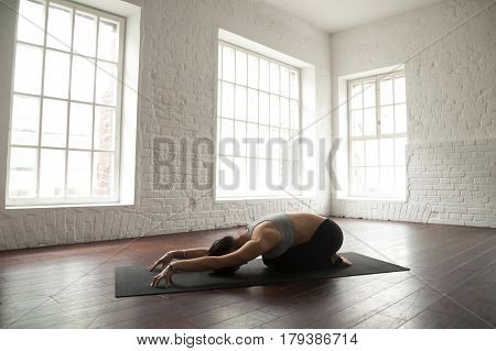 Young attractive yogi woman practicing yoga concept, sitting in Child exercise, Balasana pose, working out, wearing black sportswear, full length, white loft studio background or sports center