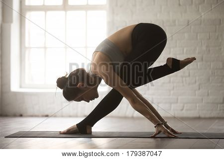 Young attractive yogi woman practicing yoga concept, standing in balance dancing exercise, working out, wearing sportswear, full length, white loft studio background, side view