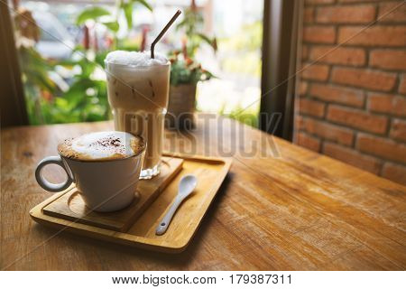 A cup of hot latte coffee and cold coffee on a wooden table. A stylish modern cafe with wooden tables and a brick wall.
