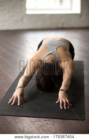 Young attractive sporty yogi woman practicing yoga concept, sitting in Child exercise, Balasana pose, working out, wearing sportswear bra and wrist bracelet studio background