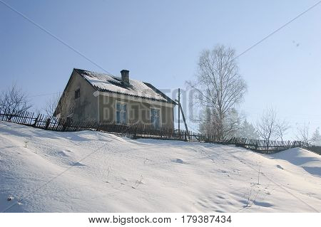 Winter landscape a small farmhouse on the Hill. The house on the roof has a chimney.