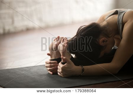 Young sporty yogi woman practicing yoga concept, sitting in paschimottanasana exercise, Seated forward bend pose, working out on black mat, studio floor background, legs and hands close up