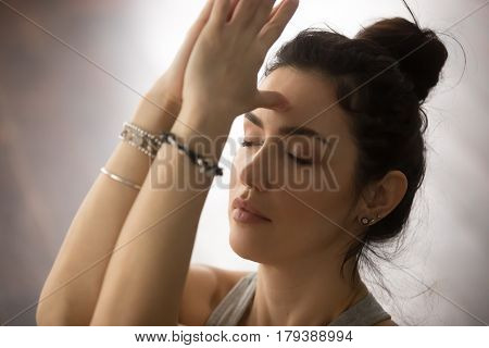 Young attractive yogi woman practicing yoga concept, doing namaste gesture, namaste hands to forehead with her eyes closed, working out, wearing wrist bracelets, studio background, closeup portrait
