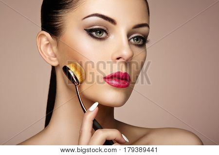 Makeup artist applies skintone with brush. Beautiful woman face. Perfect makeup. Skincare foundation. Brushes makeup artist