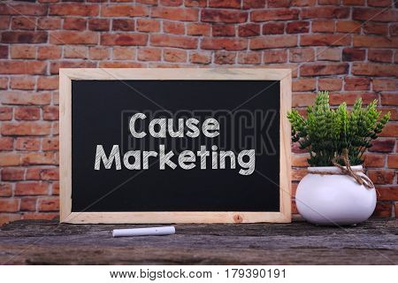 Cause Marketing Word On Blackboard With Green Plant