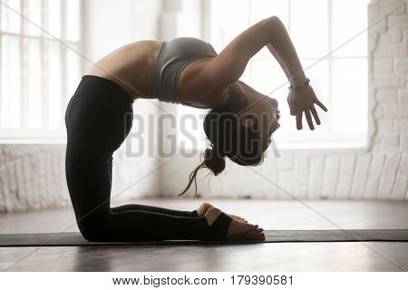 Young woman practicing yoga concept, doing Preparation for kapotasana, variation of Ustrasana exercise, Camel pose, working out, wearing sportswear, full length silhouette on loft studio background