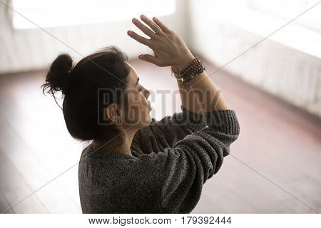 Young attractive yogi woman practicing yoga, making namaste gesture, working out, meditating wearing grey sweater, white loft studio background. Meditation session concept. Side view close up portrait