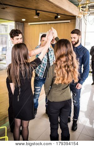 Young Group Of People High Fiving Each Other At Meeting Or Seminat Of Teamwork In Office