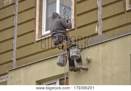 High-altitude work. The man works on high-rise works cladding, plastering of the house