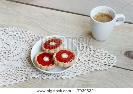 Cozy home still life. A cup of coffee and plate with cookies on knitted napkin on light wooden background. Close up.