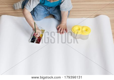 The child is going to draw watercolor paints on white paper