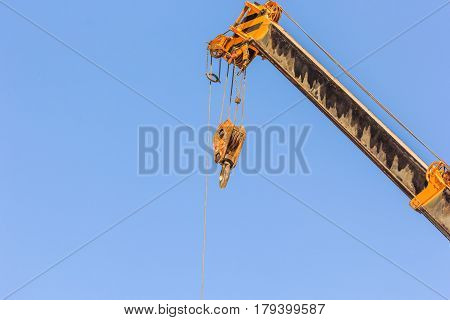 Yellow truck crane boom with hooks for lifting containers and the use of weight overboard above blue sky