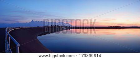 High Tatras scenery. Hydroelectric power plant Cierny Vah. Sunrise in Slovakia. Monumental peaks over water level.