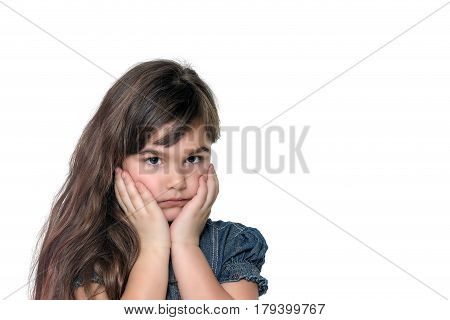 Portrait of disappointed brunette long haired little girl isolated on the white background. The girl is holding her face by both hands.