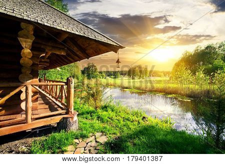 Wooden bathhouse near lake at the sunset