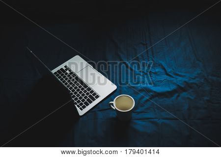 notebook and coffee cup on the blue bed.