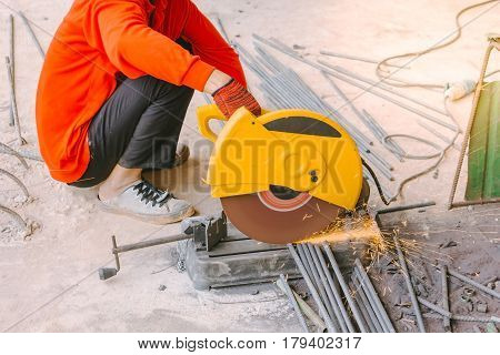 Industrial worker cutting reinforcing metal rods with many sharp sparks working on compound mitre saw with circular blade at construction building site