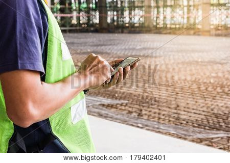 Construction worker with green helmet working on construction site using smartphone selective focus