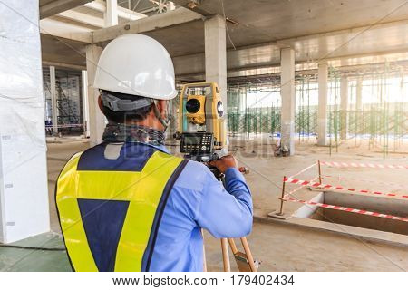 Surveyor engineer worker making measuring with theodolite equipment at construction site.