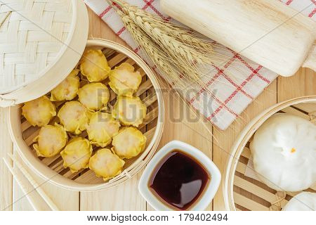 Steamed pork buns (chinese dim sum) in bamboo basket serve with chopsticks and napkin on wooden table background Top view with copy space and text.