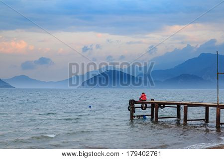 Lonely woman sitting on pier during sunset in marmaris turkey