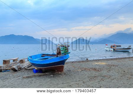 Small fishing boat on the beach of marmaris with clouds