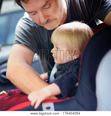 Father Helps His Toddler Son To Fasten Belt On Car Seat