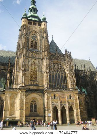St. Vitus Cathedral (Metropolitan Cathedral of Saints Vitus, Wenceslaus and Adalbert), and people on small square. Roman catholic gothic architecture cathedral in Prague, Czech Republic