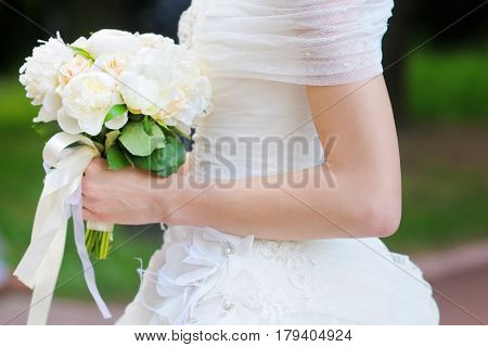 Bride holding wedding flowers bouquet close up photo