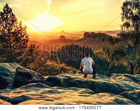 Amateur photographer takes photos with mirror camera on peak of rock. Dreamy fogy landscape spring orange pink misty sunrise in a beautiful valley below