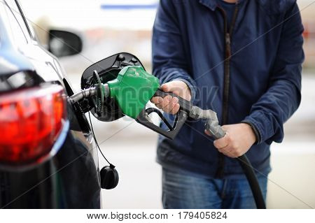 Сloseup Of Man Pumping Gasoline Fuel In Car At Gas Station