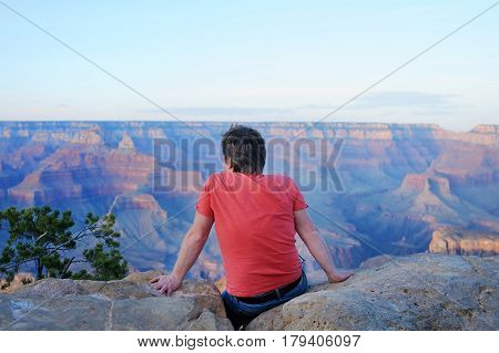Man Sitting On Stone And Looking Of The Grand Canyon