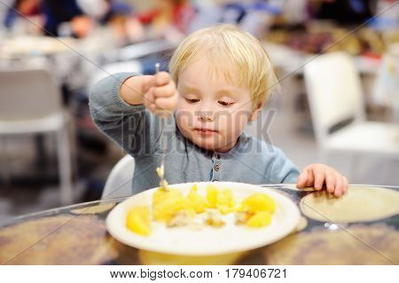 Toddler Boy Eating In Cafe